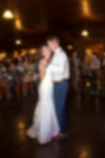 Bride and groom's first dance with guests watching