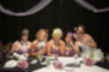 Bride and bridesmaids posing with photobooth props