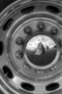 A photograph of a reflection in a hub cap of a bride and groom kissing on their wedding day