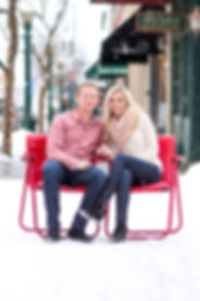 Engaged couple sitting in red chairs on a snow covered road