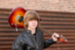 A senior boy holding his guitar over his shoulder, rusted tin all in background