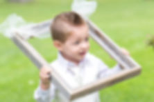 The ring bearer holding an empty picture frame over his head