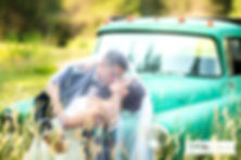 Bride and groom kissing in front of an old truck with the bride's vail covering them
