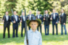 Ring bearer in front of the groom and groomsmen wearing a cowboy hat while they all hold shotguns over their shoulders