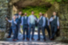 Groom and groomsmen posing under a rock archway