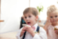 Ring bearer eating a cupcake at the reception