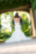 Bride and groom holding each other under a rock archway