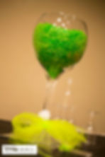 Huge wine glass full of green candy on the dessert table at the wedding reception