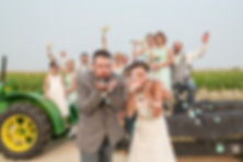 Bride and groom blowing confetti while the bridal party celebrates