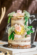 Naked wedding cake decorated with pink flowers and greenery