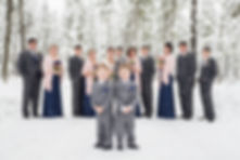 Ring bearers posing in front of the bridal party in the snow