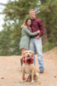 Engaged couple in the background with their dog wearing a wreath collar out front