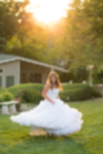 Bride twirling around in her wedding dress in the sunlight