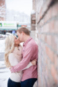 Future husband and wife kissing on a brick wall