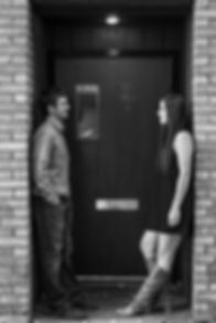 Engaged couple standing in an entry way looking at each other