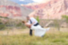 Groom dipping his bride in a meadow at Redrock State Park