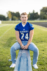 Senior boy wearing his football jersey sitting on a metal bench