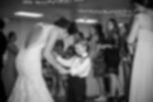 Black and white wedding photo of bride dancing with the ring bearer