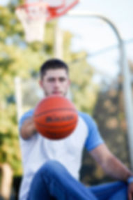 Guy palming a basketball with hoop in background