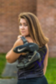 Senior girl facing away, holding her track shoes over her shoulder and looking back