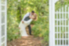 Groom dipping his bride and kissing her on a path in the forest