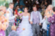 Bride and groom exiting their wedding ceremony while guests blow bubbles instead of throwing rice