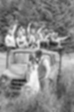 Bridal party standing in the bed of an old truck celebrating while the bride and groom kiss in front of the truck