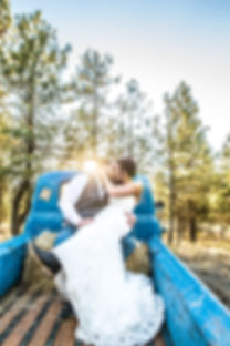 A bride and groom sitting on a hay bale in the back of an old blue truck kissing with trees and the sun in the background