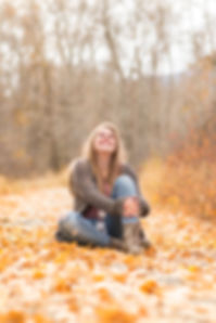A girl sitting on a path covered in yellow fall leaves, looking up at the sky