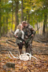 A couple posing for an engagement photo with hunting attire