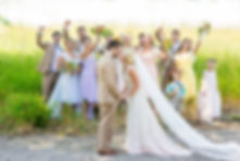 Bridal party celebrating in the background while bride and groom kiss