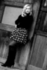 Girl leaning on old wooden wall in black and white