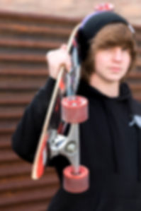 A guy holding his skateboard on his shoulder