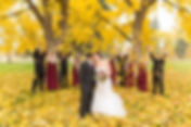 Bridal party celebrating and thowing leaves while the bride and groom kiss