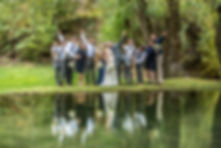 Bridal party striking a pose behind a pond with their refelection in the water