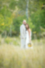 Bride and groom holding each other in a meadow with aspen trees in the background with bokeh