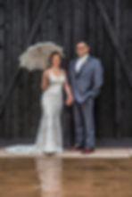 Bride and groom posing in front of barn doors