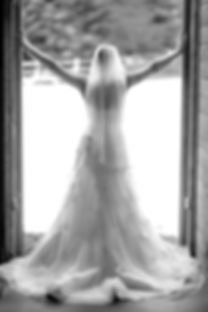 A black and white photograph of bride standing in a doorway with her back to the camera and her hands high up on either side of the doorway