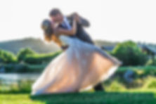 Bride and groom dancing in the grass