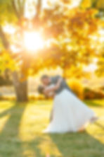 Bride and groom kissing as the sun's going down between the trees