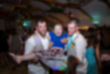 Two groomsmen dancing and carrying a little girl around the dance floor
