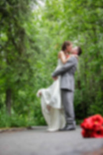 Groom lifting his bride off the ground while they kiss on a roadway with trees in the background