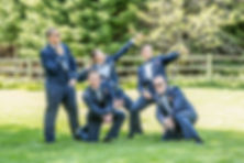 Groom and groomsmen in their dressed Navy blues striking a pose