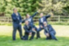 Groom and groomsmen in their dressed Navy blues striking a pose