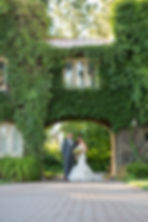 Bride and groom standing under a huge rock archway covered in greenery