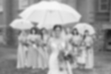 Bride and bridesmaids holding umbrellas