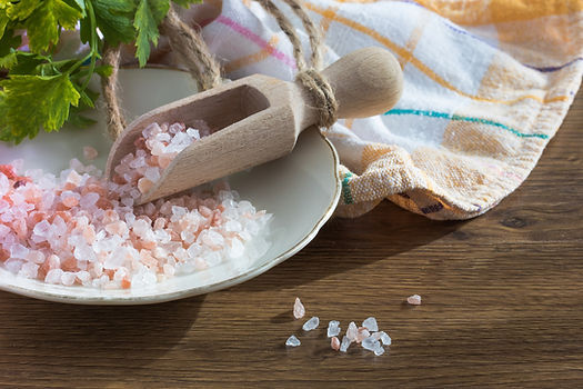 Pink Hymalayan salt on table being served with wooden spoon