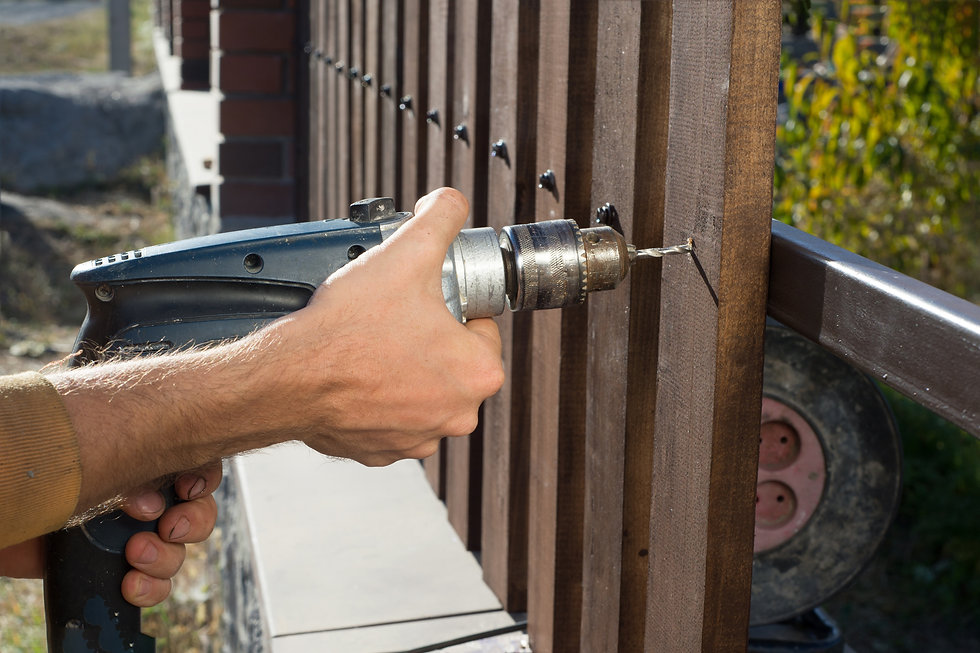Man hands drilling wooden fence to metal