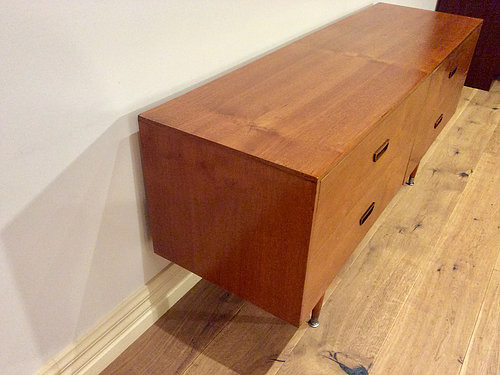 Left Side View Mid Century Danish Four Drawer Walnut Sideboard with Atomic Legs. Circa 1960.
