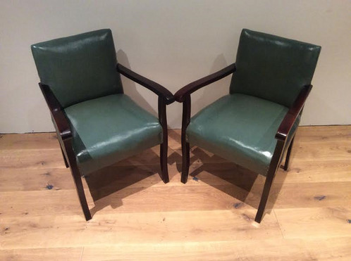 matching pair of antique armchairs with green vinyl upholstery